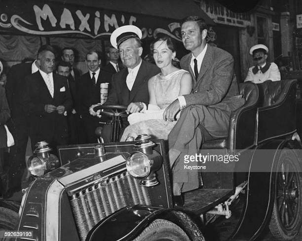 Actors Maurice Chevalier Leslie Caron and Louis Jourdan riding in an old fashioned motor car as they arrive at a reception for their film 'Gigi' at...