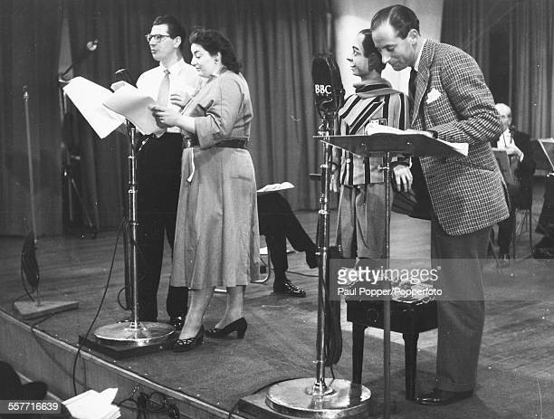 Actors Max Bygraves and Hattie Jacques with ventriloquist Peter Brough and his puppet Archie speaking in to radio microphones as they record the...