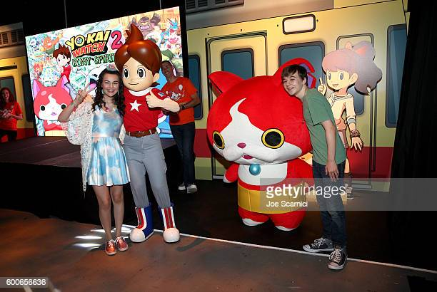 Actors Merit Leighton and Benjamin Stockham interact with costume character Jibanyan at the YOKAI WATCH 2 preview event at Siren Studios on September...