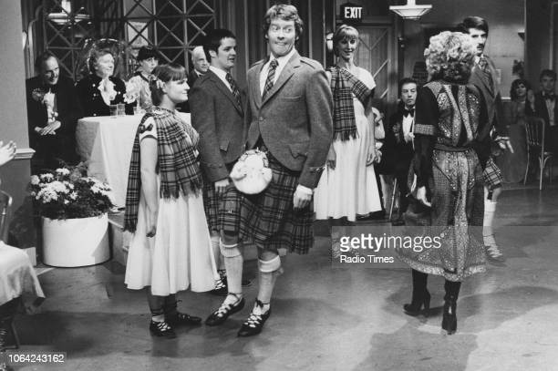 Actors Michael Crawford wearing a kilt during a group dance, in a scene from episode 'Scottish Dancing' of the television sitcom 'Some Mothers Do...
