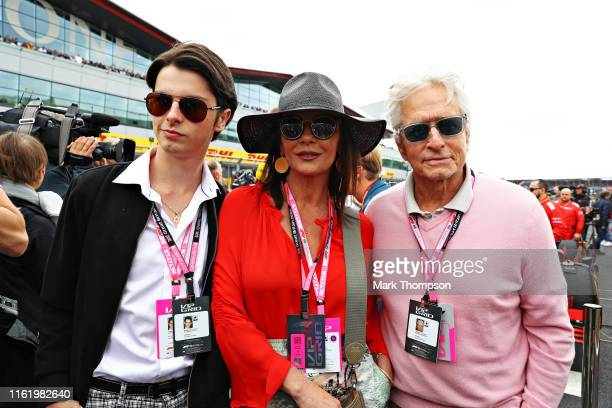 Actors Michael Douglas and Catherine Zeta-Jones and their son Dylan Douglas pose for a photo on the grid before the F1 Grand Prix of Great Britain at...