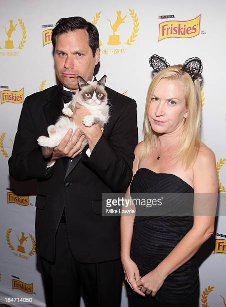 Actors Michael Ian Black and Angela Kinsey pose with Grumpy Cat at The Friskies 2013 at Arena NYC on October 15 2013 in New York City