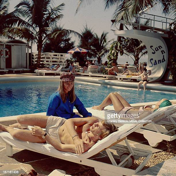 Actors Michael York and Rita Tushingham relaxing around a swimming pool during the making of the movie 'The Guru' 1969