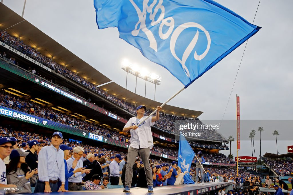 Actors Mila Kunis and Ashton Kutcher wave Dodgers flag on the dugout prior to Game 6 of the 2017 World Series between the Houston Astros and the Los Angeles Dodgers at Dodger Stadium on Tuesday, October 31, 2017 in Los Angeles, California.