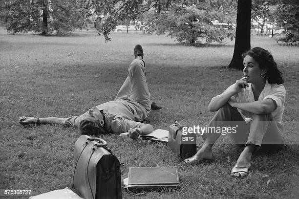 Actors Montgomery Clift and Elizabeth Taylor lounging on the grass during the filming of 'Raintree County' in Indiana 1956