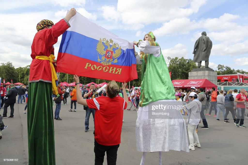 Actors on stilts carry a Russian national flag as fans gather for the opening ceremony and first match of the FIFA World Cup outside the Luzhniki stadium in Moscow, Russia, on Thursday, June 14, 2018. President Vladimir Putin has spent six years and more than $11 billion preparing nearly a dozen Russian cities to host the soccer World Cup, the biggest such event the countrys held since the collapse of the Soviet Union. Photographer: Andrey Rudakov/Bloomberg via Getty Images