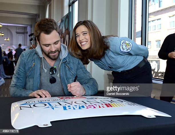 Actors Patrick John Flueger and Marina Squerciati sign a poster as they attend a press junket for NBC's 'Chicago Fire' 'Chicago PD' and 'Chicago Med'...