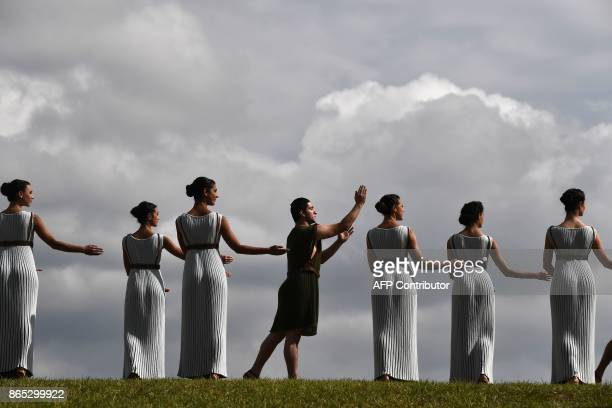 Actors perform at the Temple of Hera on October 23 2017 during a dressed rehearsal of the lighting ceremony of the Olympic flame in ancient Olympia...