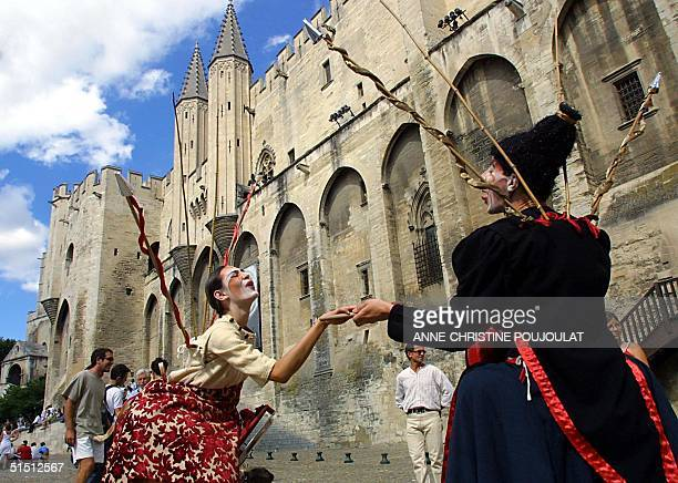 Actors perform in the street 07 July 2001 in front of the Palais des Papes in Avignon southern France during the 55th international theatre festival...