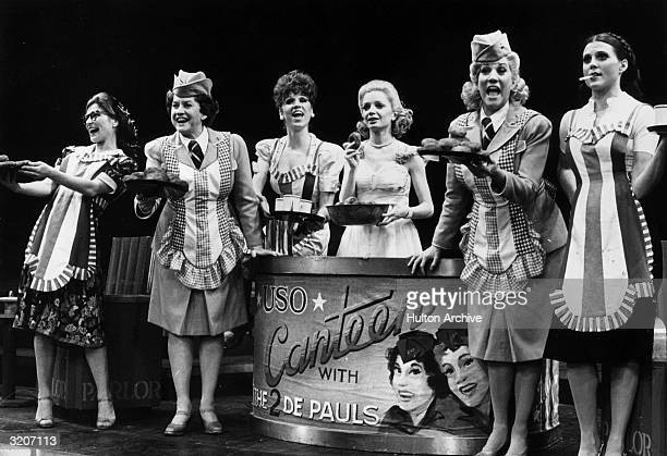 Actors Phyllis Somerville Maxene Andrews Marilu Henner April Shawhan Patty Andrews and Ann Reinking sing on stage in a production number set in a...