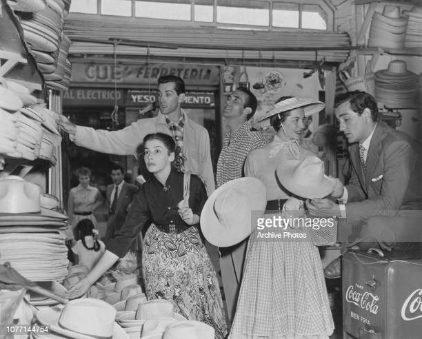 Actors Pier Angeli Vittorio Gassman Ricardo Montalban Cyd Charisse and Rick Jason visit a hat stall in the marketplace in Cuernavaca Mexico during...