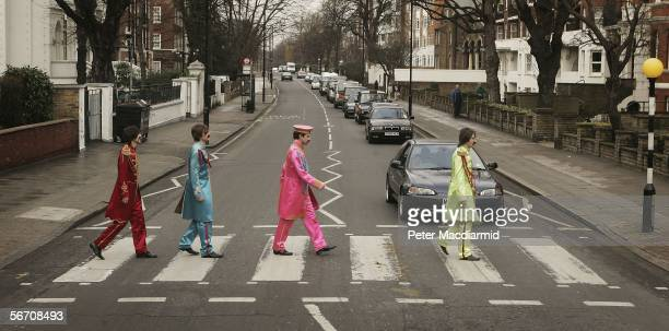 Actors play the part of the Beatles crossing a zebra crossing outside the Abbey Road studios to publicise the sale of John Lennon's original 'A Day...