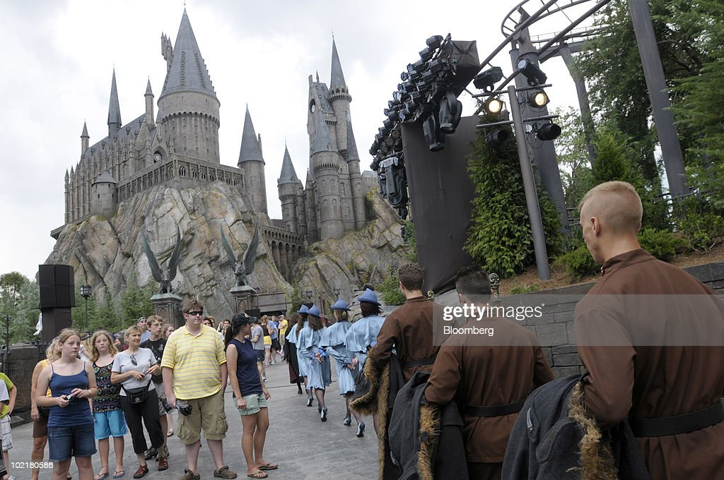 Actors portraying students from the Durmstrang Institute, in brown, and Beauxbatons Academy, in blue, march past Hogwarts castle as tourists watch at the Universal Studios Wizarding World of Harry Potter theme park in Orlando, Florida, U.S., on Thursday, June 17, 2010. Universal reportedly spent $265 million building the theme park, based on a Securities & Exchange Commission filing. Photographer: Phelan M. Ebenhack/Bloomberg via Getty Images