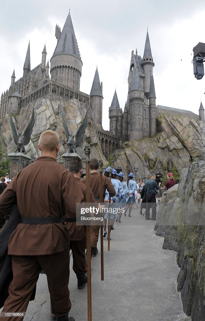 Actors portraying students from the Durmstrang Institute, in brown, and Beauxbatons Academy, in blue, march past Hogwarts castle at the Universal Studios Wizarding World of Harry Potter theme park in Orlando, Florida, U.S., on Thursday, June 17, 2010. Universal reportedly spent $265 million building the theme park, based on a Securities & Exchange Commission filing. Photographer: Phelan M. Ebenhack/Bloomberg via Getty Images