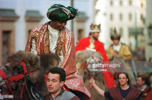 Actors posing as kings make their way on camelback through the streets of Prague's Hradcany district in Prague Czech Republic to deliver gifts to...
