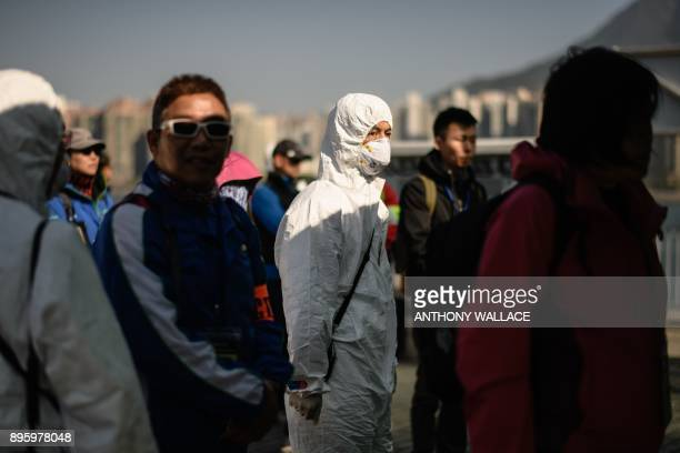 Actors posing as residents and tourists who were evacuated off Tung Ping Chau island queue for a radiation level checkpoint next to an emergency...