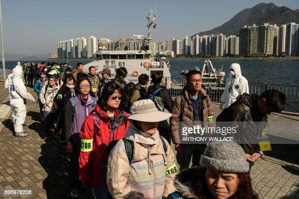 Actors posing as residents and tourists who were evacuated off Tung Ping Chau island queue for a radiation level checkpoint next to emergency workers...
