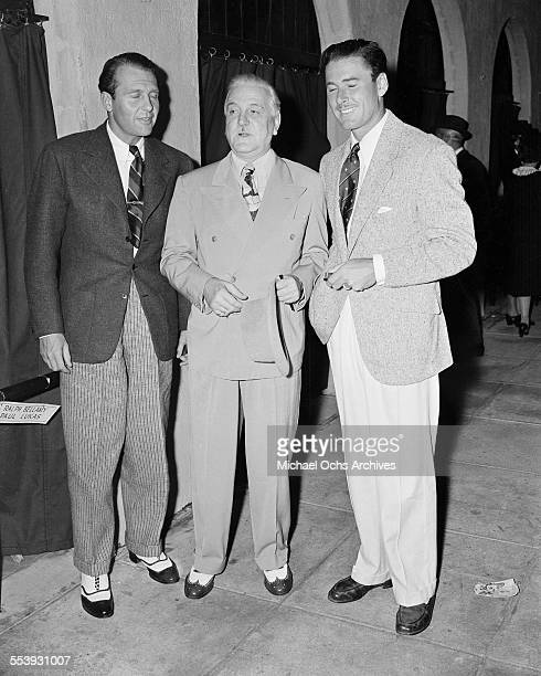 Actors Ralph Bellamy Frank Morgan and Errol Flynn seen talking on a studio back lot in Los Angeles California