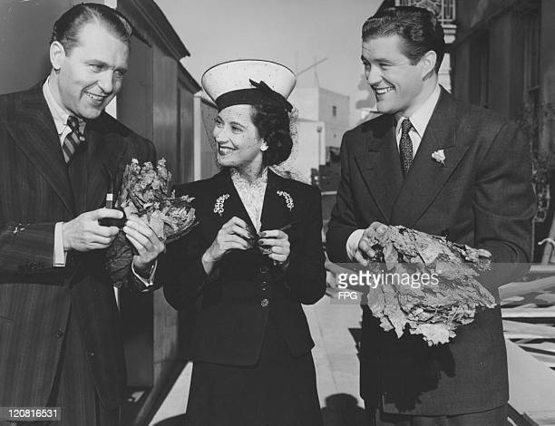 Actors Ralph Bellamy Merle Oberon and Dennis Morgan circa 1948 Morgan and Bellamy are holding what look like tobacco leaves