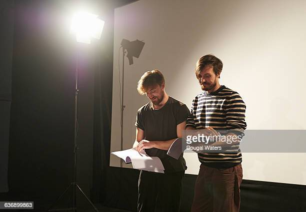 Actors reading through script on stage.