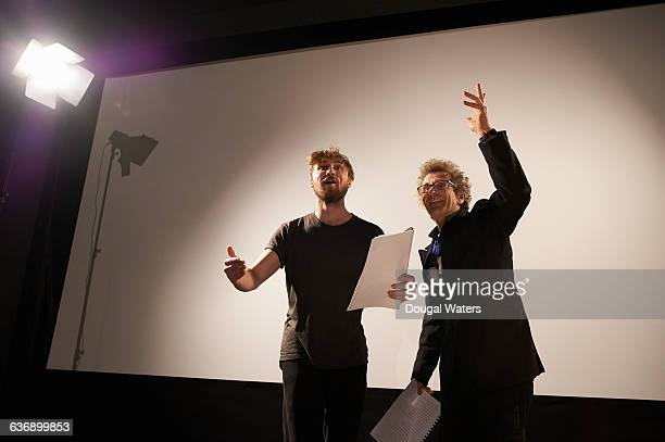 actors rehearsing on stage under spotlight. - rehearsal stock pictures, royalty-free photos & images