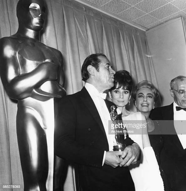 Actors Rex Harrison Audrey Hepburn Joan Crawford and George Cukor all associated with the film 'My Fair Lady' at the 37th Academy Awards Los Angeles...