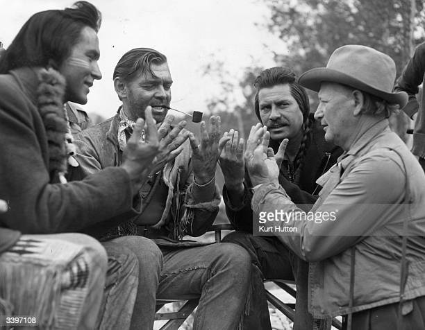 Actors Ricardo Montalban Clark Gable and John Hodiak rehearse Indian sign language with technical advisor Chief Nipo Strongheart on the set of the...