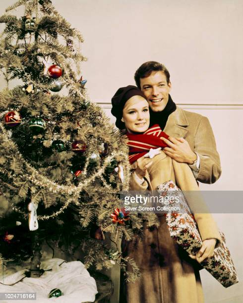 Actors Richard Chamberlain and Yvette Mimieux pose beside a Christmas tree in a publicity still for the film 'Joy in the Morning' 1965