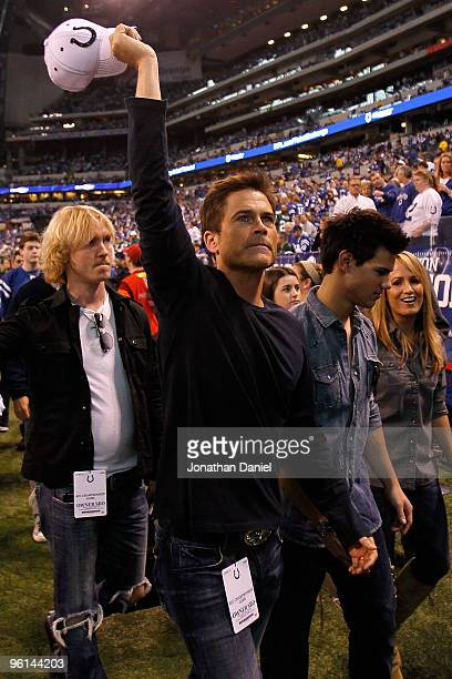 Actors Rob Lowe and Taylor Lautner walk off the field after warmups before the New York Jets take on the Indianapolis Colts during the AFC...