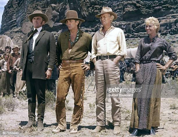 Actors Robert Mitchum Richard Widmark Lola Albright and Kirk Douglas on the set of The Way West