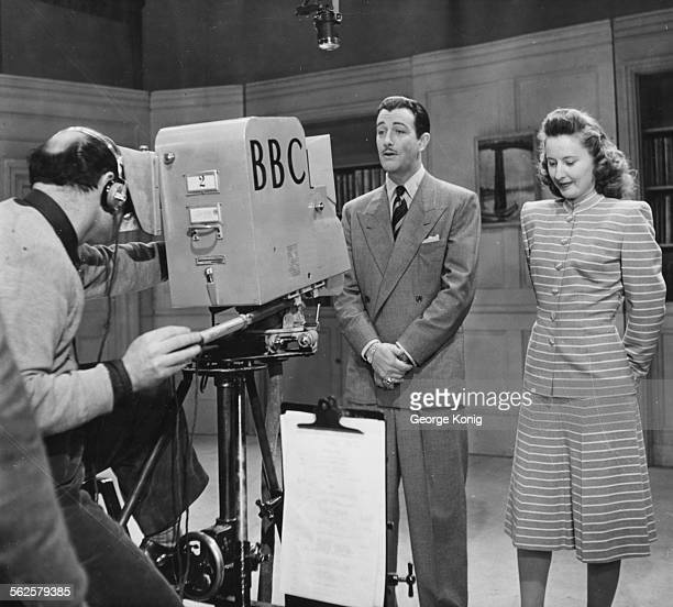Actors Robert Taylor and Barbara Stanwyck in front of a BBC Television camera on set circa 1950