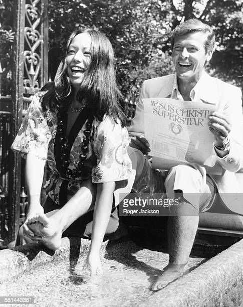 Actors Roger Moore having his feet washed in a horse trough by actress Yvonne Elliman, jokingly promoting the film 'Jesus Christ Superstar', in Park...