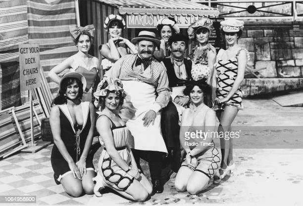 Actors Ronnie Barker and Ronnie Corbett surrounded by scantily clad women in the 'seaside sketch' from the television comedy series 'The Two Ronnies'...