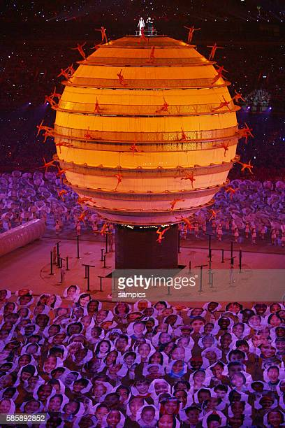 Actors run on an elevated Globe while Sarah Brightman from Britain and Chinese Popstar Liu Huan perform on the top the theme Song 'You and Me' during...