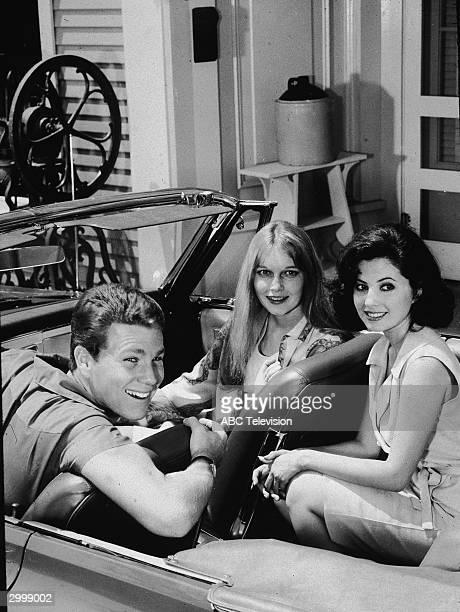 Actors Ryan O'Neal Mia Farrow and Barbara Parkins smile while sitting in a convertible automobile in a still from the TV series 'Peyton Place' circa...