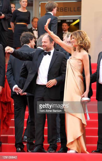 Actors Samuel Labarthe and Florence Pernel wave to fans as they attend the La Conquete Premiere during the 64th Annual Cannes Film Festival at the...