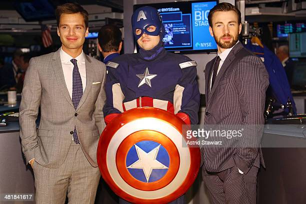Actors Sebastian Stan and Chris Evans pose with Captain America during The NYSE Opening Bell at New York Stock Exchange on April 1 2014 in New York...
