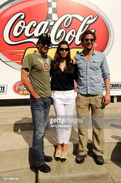 Actors Sharlto Copley Jessica Biel and Bradley Cooper pose in Victory Lane prior to the start of the NASCAR Sprint Cup Series CocaCola 600 at...