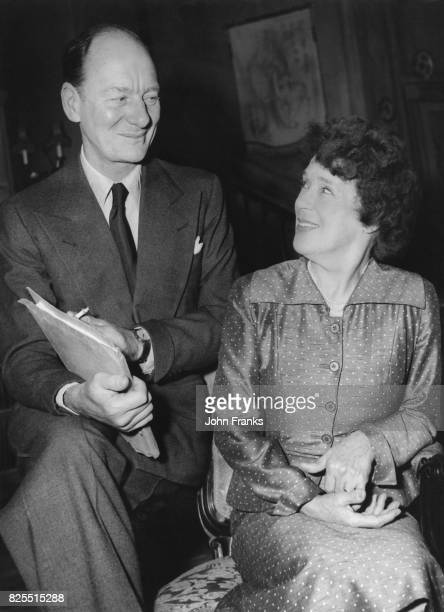 Actors Sir John Gielgud and Kathleen Harrison discuss the script for Noel Coward's new comedy 'Nude With Violin' during rehearsals at the Olympia...
