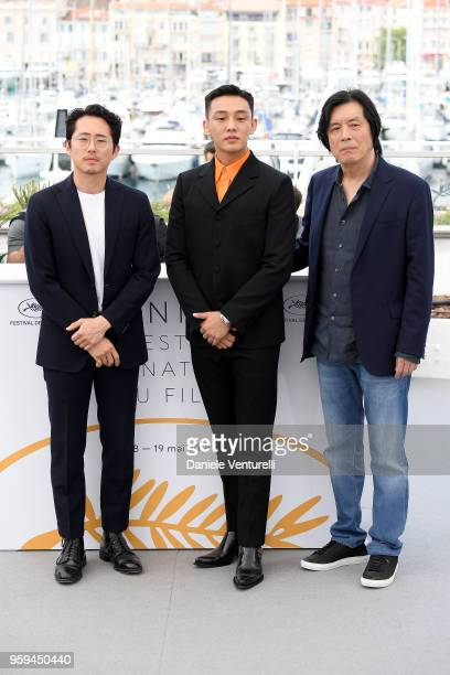 Actors Steven Yeun Ahin Yoo and director Lee Changdong attend the photocall for the 'Burning' during the 71st annual Cannes Film Festival at Palais...