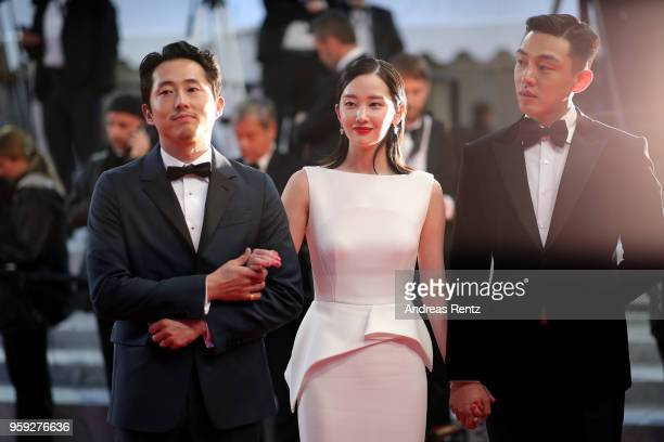 Actors Steven Yeun Jongseo Jeon and Ahin Yoo depart the screening of 'Burning' during the 71st annual Cannes Film Festival at Palais des Festivals on...