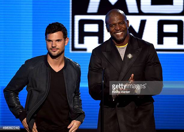 Actors Taylor Lautner and Terry Crews speak onstage during the 2015 American Music Awards at Microsoft Theater on November 22 2015 in Los Angeles...