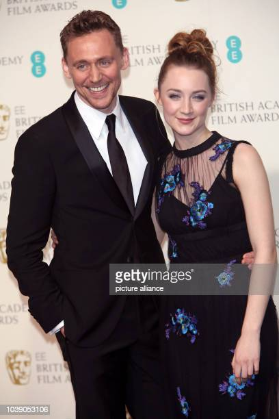 Actors Tom Hiddleston and Saoirse Ronan pose in the press room of the EE British Academy Film Awards at The Royal Opera House in London England on 10...