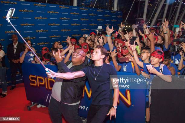 Actors Tom Holland and Jacob Batalon pose for a selfie with fans during the SpiderMan Homecoming event at Marina Bay Sands on June 6 2017 in Singapore