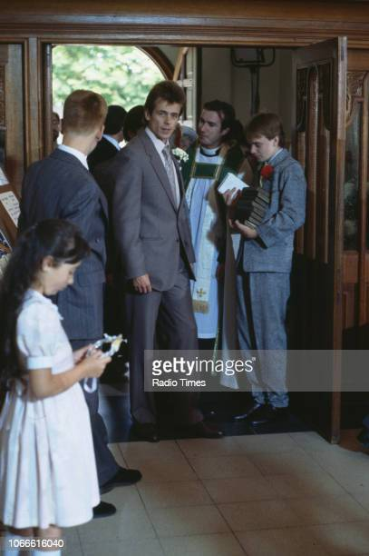 Actors Tom Watt and Adam Woodyatt pictured during filming on a church set for the BBC soap opera 'EastEnders' circa 1986