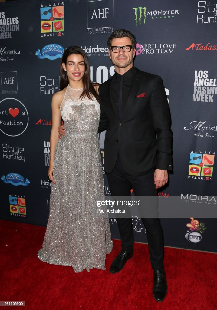 Actors Tonia Sotiropoulou (L) and Christos Vasilopoulos (R) attend the Domingo Zapata Fashion Show at the Los Angeles Fashion Week 10th season anniversary at The MacArthur on March 12, 2018 in Los Angeles, California.