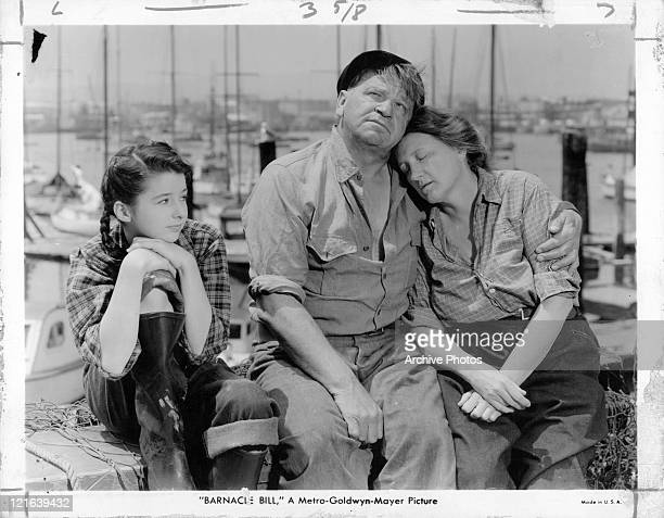 Actors Wallace Beery and Marjorie Main sitting at a dock with child actress Virginia Weidler in a scene from the film 'Barnacle Bill' 1941