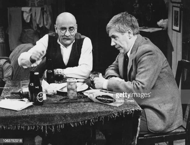 Actors Warren Mitchell and Alfie Bass eating and drinking at a table in an episode of the television show 'Till Death Us Do Part' January 12th 1975