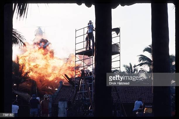 Actors watch a fire burn during the filming of 'Apocalypse Now' April 28 1976 in the Philippines The movie directed by Francis Ford Coppola and based...