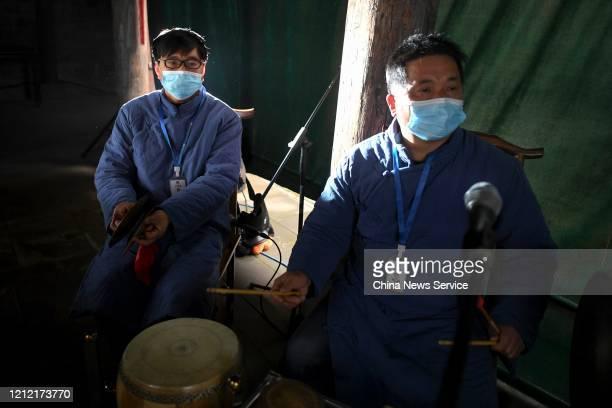 Actors wearing face masks play traditional musical instruments accompanying a Huagu Opera, a Chinese opera originating in Hunan province, at the...